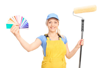Woman holding a paint roller and a color guide