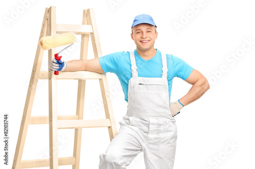 Cheerful male decorator holding a paint roller - 82103744
