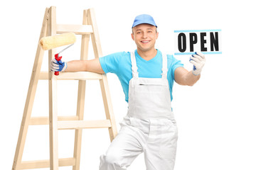 House painter holding a paint roller and an open sign