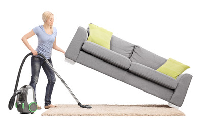 Housewife lifting a sofa and vacuuming underneath it