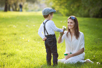 Beautful kid and mom in spring park, flower and present. Mothers