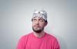 Bearded funny man in a cap of aluminum foil.