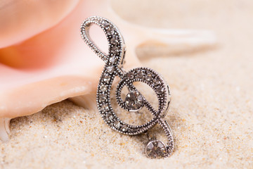 Violin key treble clef in sand