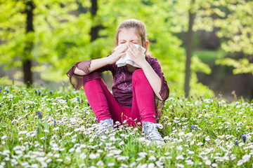 Little girl with allergy symptom blow her nose