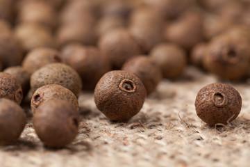Allspice pepper seeds close up texture on vintage textile backgr