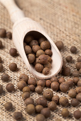 Whole allspice pepper super food in a wooden spoon on vintage te