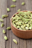 Green cardamom ayurveda asian aroma spice in a wooden bowl on vi