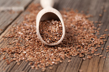 Vegetarian nutrition flax seeds with omega fat in spoon on vinta