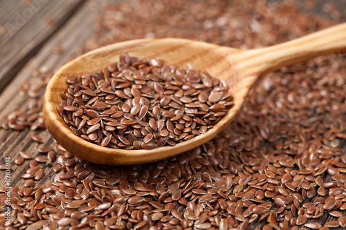 Heap of flax seeds in vintage wooden spoon