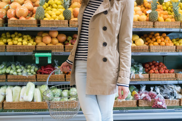 Girl in the supermarket chooses vegetables and fruits