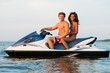 Multinational couple sitting on a jet ski