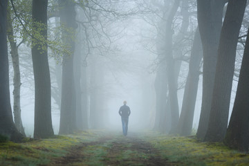 Man walking in a mysterious lane on a foggy and dark morning.