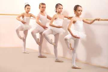 Group of four little ballerinas practicing