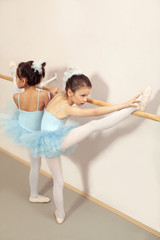Two little ballerinas practicing and stretching with stick