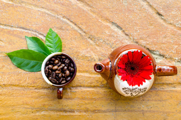 Coffee beans in a mug & kettle with flower and leaves top view