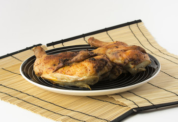 Roasted chicken on a striped black dish on a bamboo mat