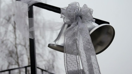 Wedding bells on a railing blowing in the wind.