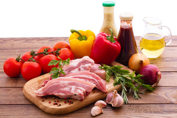 Food. Raw meat for barbecue with vegetables on wooden surface.