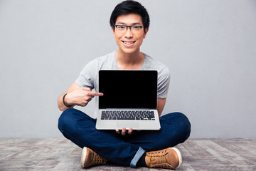 Smiling asian man showing finger on laptop screen