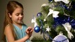 Child near white Christmas tree.