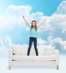 smiling little girl jumping on sofa