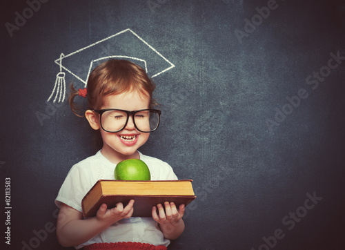girl schoolgirl with books and apple in a school board - 82113583