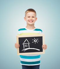 happy little boy holding chalkboard with home