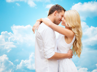 happy couple hugging over blue sky