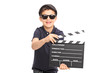 Little boy having fun with a movie clapperboard