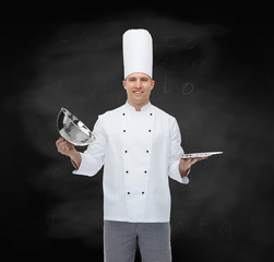 happy male chef cook opening cloche