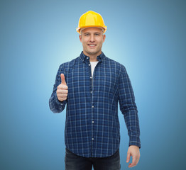 smiling male builder in helmet showing thumbs up