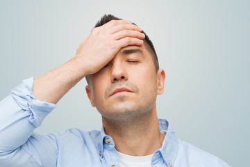 unhappy man with closed eyes touching his forehead