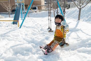 冬に公園のブランコで遊ぶ子供