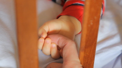 sleeping baby's hand and stroked father's hand close-up