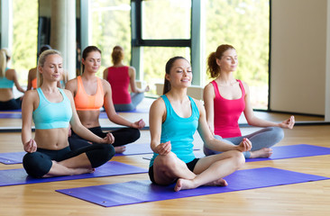 smiling women meditating on mat in gym