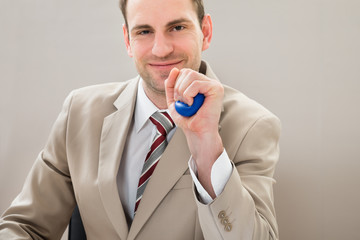 Businessman Squeezing Blue Stressball