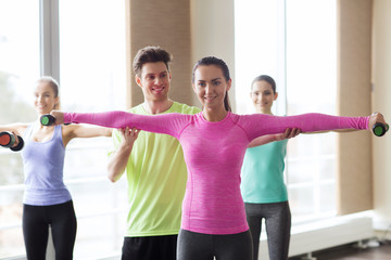 happy women and trainer with dumbbells in gym