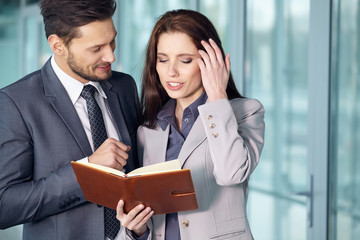 Young Business couple looking at file indoors.