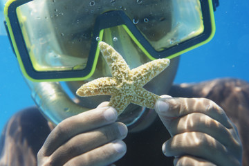 Hispanic boy in goggles holding starfish