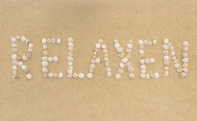 Wort RELAXEN aus Schneckenhäuschen im Sand