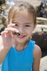 Asian girl holding tiny crab