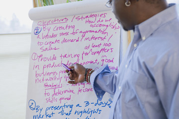 African man pointing at text on flip chart