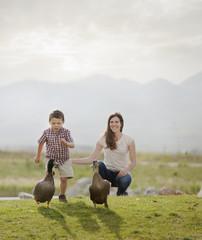 Caucasian mother and son feeding ducks