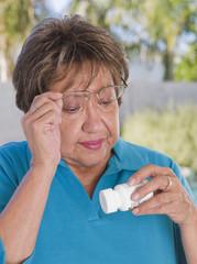 Senior Hispanic woman reading medication bottle