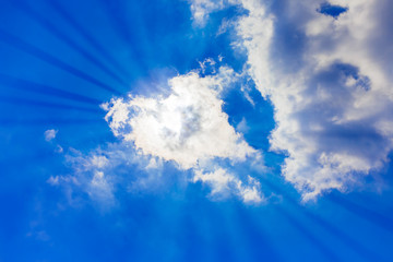 Bright blue sky with clouds and sunlight