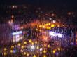 Night city lights behind rainy window