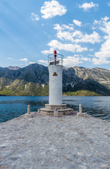 White lighthouse tower on the island in Bay of Kotor