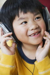 Asian boy listening to headphones