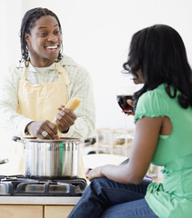 African couple cooking in kitchen