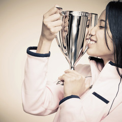 Mixed race woman holding trophy